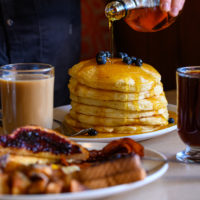 Person pours maple syrup over a stack of pancakes. Coffee, tea, toast and hash browns are in the foreground.
