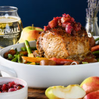 Pork roast with cider chutney on top. Sitting in white platter with a glass of Bulwark cider in background.