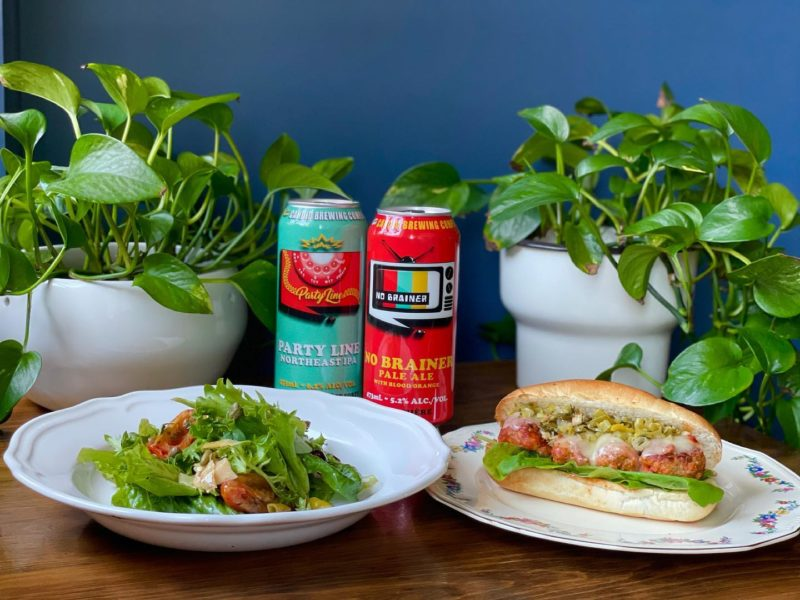 A salad and a meatball sub sit on white plates with two beer in the background centre and two potted green plants on each side.