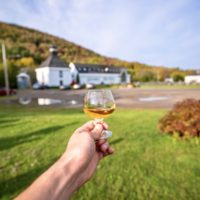 hand holds a dram of whiskey in front of glenora