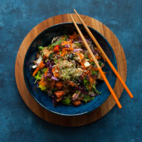 blue bowl filled with a vegetable dish sits on a wooden platter on top of a blue background. two wooden chopsticks are on the bowl.